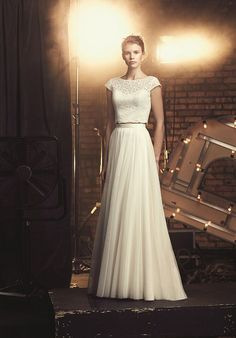 Mikaella Lace and Mesh Tulle Wedding Dress. Cropped lace bodice with bateau neckline and cap sleeves with modified sweetheart neckline on lining. Fabric covered buttons along center back of bodice. Full tulle skirt. Invisible zipper.