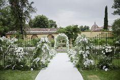 White Enchanted wedding aisle with greenery and flower decorated arch, iron gates decorated with natural elements