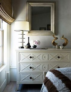 More brown and cream/ivory repeated.  Ivory dresser with bronze knobs, lamp with brown linearity, afghan.  Simplicity made effective through repetition.  Unforgettable.  Steven Gambrel.