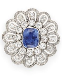 A BELLE EPOQUE SAPPHIRE AND DIAMOND BROOCH. Bezel-set with a cushion-cut sapphire, within a collet-set diamond surround, to the rose and old European-cut diamond daisy motif frame, mounted in platinum, circa 1910.                                                                                                                                                     More