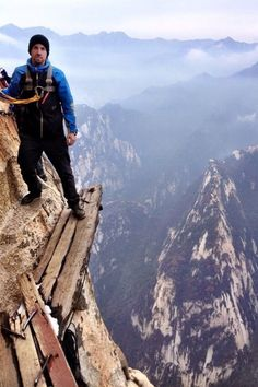 "Hiking Mount Hua! Climbers clip onto chains as they hug the rock face at peaks of up to 7,070 feet. What's more terrifying: the wooden walking path that is less ""bridge"" and more ""lip on the cup of your sanity."""