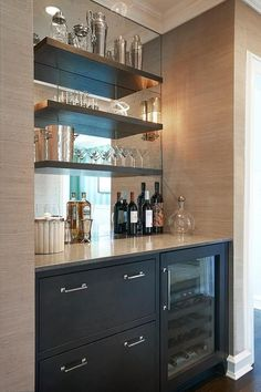 Chic butler's pantry boasts a nook filled with grey cabinets fitted with a glass-front beverage fridge placed under grey floating shelves lining a mirrored backsplash.