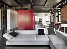 Nagy lakás egyedi lakberendezési megoldásokkal, sok fa elemmel és egy látványos piros konyha-gardrób tömbbel