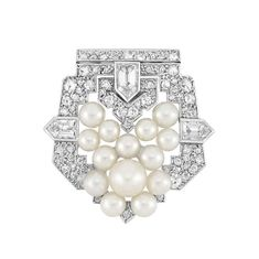 Art Deco Platinum, Pearl and Diamond Clip   The pierced shield mounting set throughout with numerous small rose-cut and 2 old-mine cut diamonds, accented by 3 bullet-shaped diamonds approximately .90 ct., centering one pearl approximately 6.4 mm., surrounded by a cluster of 13 pearls approximately 4.6 to 3.4 mm., with French assay marks, circa 1925