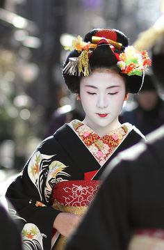 Maiko Korin make her way round the tea houses of the Miyagawa-cho district in Kyoto, Japan to wish people a happy new year. 2012, Japan.