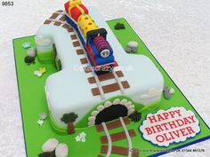 Childrens first birthday number 1 Thomas the Tank engine cake. Hand cut for larger portions topped with a hand modelled Thomas character with present cargo. Decorated in a fun style with tunnel and track complete with steam effect message http://www.cakescrazy.co.uk/details/thomas-the-tank-engine-number-one-shaped-cake-9853.html