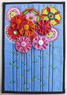 Such a pretty quilt w/ a bunch of pretty yo yo flowers.