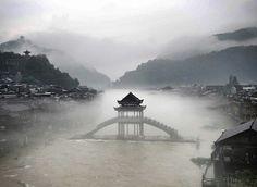 洪水退去后的凤凰古城,雨雾笼罩着远处的山林,沱江「雪桥」和临岸的古建筑在雾霭中若隐若现,中国 China 湖南省 Hunan。统计显示此次洪灾直接经济损失达3.05亿元。摄影师:Yanmin Liu