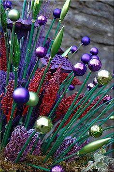 Christmas ornaments glued on a small painted dowel. Whimsical and pretty garden decor.