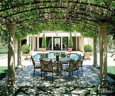 Positioned by the pool and with sunlight filtering through its vine-clad roof arches, this pergola is a comfortable dining venue even on the hottest summer days. The metal in the overhead structure has a lighter look than wood and is echoed in the wrought-iron dining set./