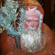 This late 19th century German Santa has a very rare beard made of glass icicles. He has a serious, concerned expression on his face.