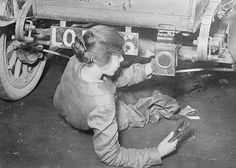 A female mechanic reclines under a car while performing repairs to the vehicle, 1917.