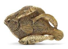 An ivory netsuke of several edible fish By Moritoshi, late 19th century A large dead flat-fish resting with three smaller fish draped over its body and two others beneath, forming a still-life composition of somewhat flattened form in lightly-stained ivory, signed Moritoshi.