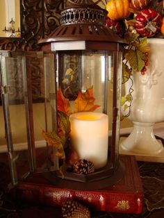 candle in the glass lantern with just a couple of leaves and pinecone