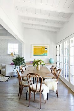 love the white brick wall and long table with fur over the chairs.