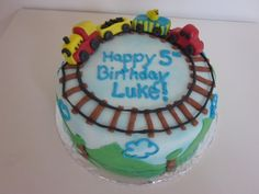 """Train Cake: rectangle, green frosting for """"grass"""", tracks on top, leading up to a circular play train on a small """"smash cake"""", picks with train signs along the tracks..."""