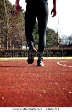 Young man walking on sports track after workout