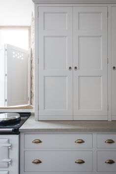 Dorset Farmhouse Kitchen by Plain English featuring cupboards with Honed Oyster Stone worktops. Antique Georgian Drop Ring and Plain Drawer Pull Brass Handles.
