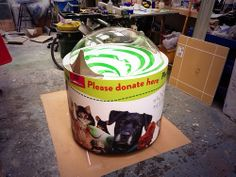 Coin spiral donation box with spiral graphic and acrylic dome.