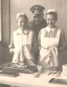 WWII German Red Cross Nurses.  Although the two nurses are smiling at the Sergeant's antics, I am sure they must be rather annoyed by his presence, particularly as they appear to be preparing sterilised equipment . . .