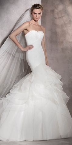 This wedding dress was inspired by plumage to create a beautiful sweetheart neckline with feathers. From this neckline, a pleated tulle bodice wraps the mermaid silhouette that ends in a tulle and nylon skirt full of movement and frills.