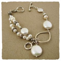 """This delightful multi-strand bracelet is strung with a variety of hand picked pearls interspersed with silver oxidized beads. Two playful charms hang from the center point of this piece, making for a fun companion for long walks on the beach.  71/2"""" L. with toggle clasp."""