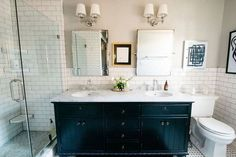 The master bathroom continues the kitchen's elegant monochromatic color scheme and features mirrors, lighting, and cabinetry purchased at Restoration Hardware.