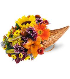 Brighten your table with a colorful, celebratory cornucopia array! A joyful symbol of Thanksgiving, this arrangement is perfect for your gathering, or as a gift for your host!   A bountiful mixture of lilies, sunflowers, Gerbera daisies, mums, and more are arranged in a wicker cornucopia horn basket.  highlandmiflorist.com accentsofeden.com