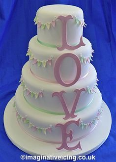 """Because there aren't enough cakes with buntings on them. In brighter colors and without the word """"love"""" it'd be a great circus themed cake too"""