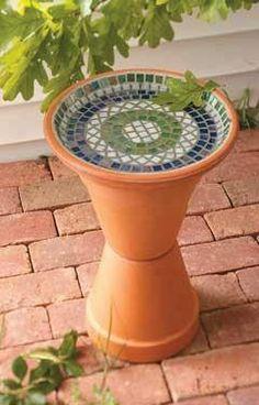 Dois vazos e um prato de cerâmica fazem um bebedouro para passarinhos ou uma mesinha.