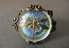 AB czech glass dragonfly button sits in a brass setting atop a brass filigree wrap.