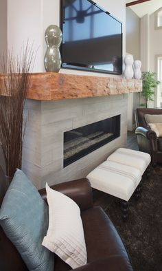 Fireplace with concrete tiles with pattern to imitate barn board.  Mantel is from the original horse stalls, complete with chew marks.