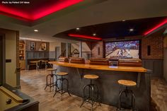 A real man cave with everything a man could want. You have the stadium seating with eight recliners, a bar behind, the pool table and extra seating on the side. Not a bad spot spot to watch the NCAA tournament. #man #bars