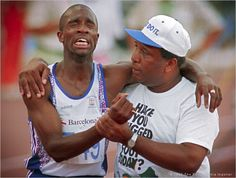 """Derek Redmond is helped towards the finish by his father after an injury in the 400m semi at the Barcelona Games. Redmond collapsed about half way through the race with the injury, but got up, determined to finish despite the pain. His father, Jim Redmond, had rushed down from the stands. Redmond initially tried to push him away, not realizing who he was, but then heard a familiar voice: """"Derek, it's me."""""""