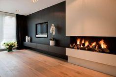 Bellissimo camino a legna di grandi dimensioni presente in un living moderno bianco e nero