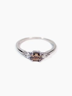 Mach: Bella Ring brown diamond. 14k white gold, cognac diamond ring. This delicate engagement has an air of Parisian glamour, with an emerald cut centre diamond, set with tiny pear shaped diamonds on either side. #engagementrings #weddingjewelry #wedding #finejewelry #customengagementrings
