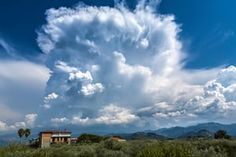 Cumulonimbus are heavy, dense clouds in the form of a mountain or huge towers, such as these in Pace del Mela, Messina, Italy. At least part of the upper portion is usually smooth, or fibrous or striated and nearly always flattened. The cloud base is often very dark. In this image, the upper portions have a cirriform appearance identifying the species as capillatus and an anvil is in the early stages of development which is the supplementary feature incus.