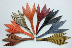These NOS quill feather fancy trims still have the Paris label of origin attached to them. They are constructed of multicolored hand dyed feathers quills meticulously pasted onto a fabric backing. They are in mint condition, but delicate due to the age of the glue and need to be