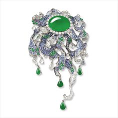 JADEITE, DIAMOND AND GEM-SET BROOCH  Designed as a cascading flower, centring on an oval-shaped jadeite cabochon of emerald green colour and high translucency, framed by circular-cut diamonds with vines decorated by round sapphires, emerald beads and icy jadeite beads