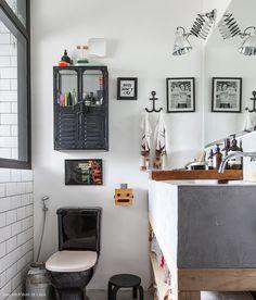 Banheiro com bancada de concreto, gabinete feito com madeira pinus e armarinho industrial preto.