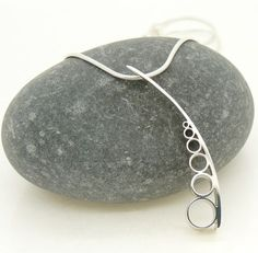 This is a contemporary, stylish, sterling silver pendant from Claire Wood Jewellery with a multiple circles motif. Inspired by the beautiful repeated shapes of the internal structure of a Cerith shell. lazydoggallery.com
