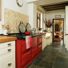 Open plan country kitchen. Check on the red stove and the dark tile! I also like the floral arrangement in the corner.