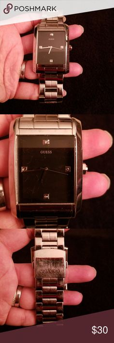 Men's GUESS Watch Water resistant and stainless steel watch. Black face with a small diamond in the 12. Scratches from normal wear and storage. Needs a battery. Scratches on the face can't be seen when worn and doesn't interfere with reading the time. Smoke and pet free home. Please let me know if you need additional pictures. Last pic is to show size on my wrist. But this is my husband's watch so no links have been taken out. Guess Accessories Watches