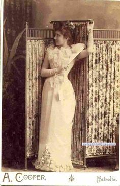 A young dancer's postmortem photograph. The lady is dead, and is posed using a metal rod alongside her spine, and her hand is actually strapped to the screen behind her using wire, making it appear as if she is posing by herself.