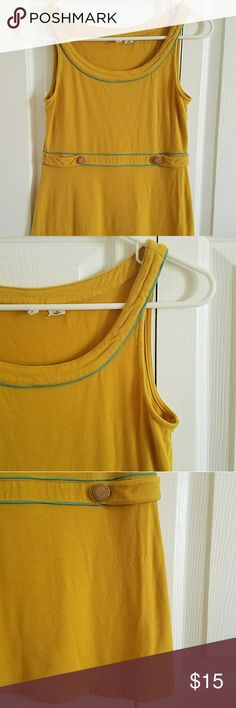 MOTH Mustard Babydoll Tank Top ANTHROPOLOGIE Women's MOTH babydoll tank top. Size Small. Mustard in color with teal trim along the waist & neckline. Decorative wooden buttons adorn both sides of the waist. Stretch. 92% rayon, 8% spandex. Purchased from Anthropologie.  Measurements (while lying flat): Shoulder to shoulder- 11 1/2 inches Armpit to armpit- 15 inches Sleeve length- n/a Top to bottom hem- 23 inches  PREOWNED. Gently worn. Buttons have minor scuffs. No rips, stains or…