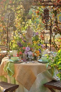 Garden statue centerpiece surrounded by lilac roses, azaleas, spring garden blooms