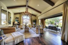 Contemporary Living Room with Exposed beam, Chandelier, Arched window, Hardwood floors