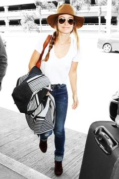 Olivia Wilde's airport outfit is something you can actually recreate: comfy jeans, slouchy tee, cozy poncho / sweater, and black booties for style