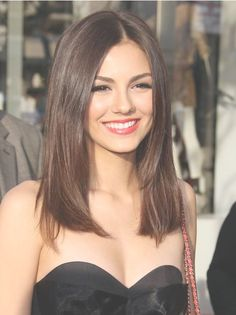 Straight natural brown hair cut below shoulders' line.