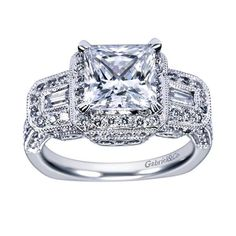 You don't have to choose one ring over another when your Gabriel ring has it all. Two baguette cut diamonds make this a three stone engagement ring around a princess cut stone at the center and a pave of light catching diamonds around the halo.